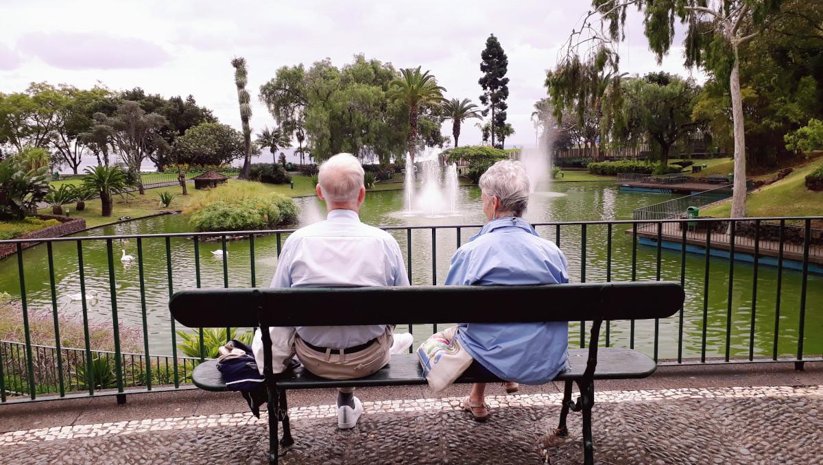 Iäkäs pariskunta istuu penkill' katselleen lampea